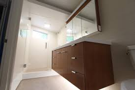 White Bathroom Wall Cabinets With Glass Doors by Cream Granite Floor With White Toilet Brown Wooden Bathroom