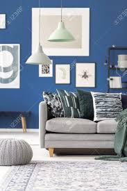 pastelllen über grauer mit kissen gegen blaue wand mit galerie im wohnzimmer mit puff