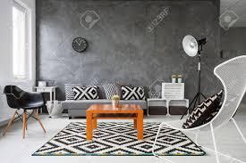 wohnzimmer mit grauen wänden und weißen holzparkett schwarz weiß dekorationen mit orangefarbenen couchtisch in der mitte des raumes
