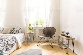 moderner stuhl tisch mit kerzen und bett mit floralen decke in ein einfaches schlafzimmer innenraum stockfoto und mehr bilder behaglich