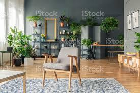 vintage grauen sessel in der mitte eine tropische wohnzimmer interieur mit vielen pflanzen auf dem holzboden und schwarzen rack stockfoto und mehr