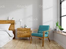 modernen mitte jahrhundert und vintage interieur aus schlafzimmer blue lounge chair mit holz nachttisch und weißen bett auf weiße wand und holzboden