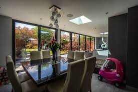 Internal Dining Area Looking Out Onto The Rear Garden Through Aluminium Bifold Doors In Grey RAL 5016 Light Is Also Brought Into Space Via Two Small