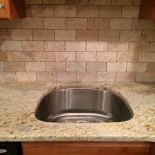 granite counter tops with tumbled marble subway tile backsplash