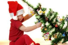 Baby Decorating A Small Tabletop Christmas Tree