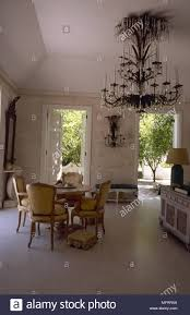 Traditional Dining Room With High Ceilings Stone Walls Marble Floor Round Antique Table And Chairs An Ornate Crystal Chandelier