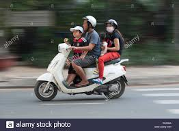 Four Person Family On Scooter Motorcycle In Ho Chi Minh City Vietnam Two Young Children Eating