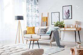 graue decke auf beige im hellen wohnzimmer mit boho muster auf vorhängen und kissen