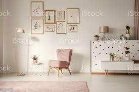 altmodische sessel pastell rosa stehleuchte und stilvolle goldene verzierungen in einem retrowohnzimmer interieur mit weißen wänden stockfoto und mehr