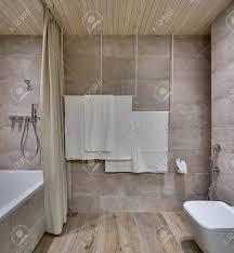 modernes badezimmer mit strukturierten fliesen und einer holzdecke es gibt ein weißes bad mit einem vorhang und einer dusche handtuchhalter
