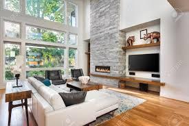schönes wohnzimmer mit parkettboden und kamin im neuen luxus haus hat sehr hoch gewölbter decke und bank fenstern zusammen mit boden bis zur