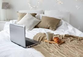 technologie feiertags weihnachts und winterkonzept gemütliches schlafzimmer mit laptop computer kaffeetasse und hörnchen auf bett am