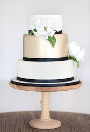 black and white wedding cake with brushed gold gum paste magnolia and navy ribbon