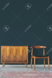 holzmöbelschrank und stuhl in der weinleseart gegen dunkelblaue wand im stilvollen wohnzimmer mit wolldecke