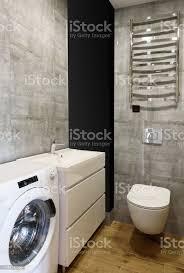 moderne badezimmerinterieur mit wc weißespüle waschmaschine graue fliesen an denwänden und holzboden kopierraum stockfoto und mehr bilder