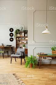 mitte des jahrhunderts moderne sessel in eine graue wohnzimmer einrichtung mit holzmöbeln arbeitsbereich und vintage dekor echtes foto stockfoto und