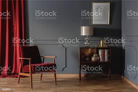 echtes foto einer ecke des eine retrowohnzimmer einrichtung mit eleganten beige le auf einem hölzernen schrank neben einem roten sessel