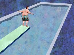 Man Standing On Edge Of Diving Board Over Swimming Pool