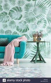 rosa decke auf blauen sofa neben einem tisch mit anlage