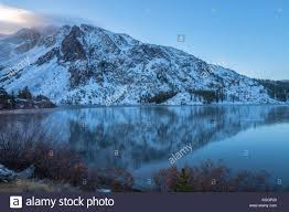 Sierra Nevada Mountains Cover With Snow And Its Reflection On The Frozen Ellery Lake In Early Winter Tioga Pass California