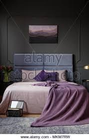 lila decke auf dem bett im dunklen schlafzimmer innenraum
