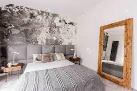 graues kingsize bett in einem geräumigen schlafzimmer mit einer abstrakten tapete an der wand und einem großen spiegel mit holzrahmen