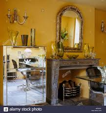 A Detail Of Modern Yellow Dining Room With Fireplace Deco Mirrored Chest Drawers Glass Vases