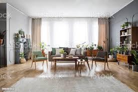 echtes foto einem geräumig vintage wohnzimmer interieur mit einem sofa zwischen zwei stühlen und hinter dem tisch die neben einem schrank mit
