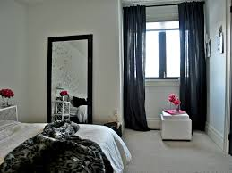Leaner Mirror With Black Frame Before The White Wall Plus Curtain And Bedding For