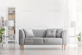 le auf silber tisch neben grauen sofa mit kissen in weiß wohnzimmer interieur mit anlage echtes foto stockfoto und mehr bilder behaglich