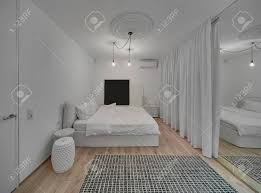 modernes schlafzimmer mit weißen wänden und ein parkett mit einem teppich auf dem boden es gibt ein bett mit weißen kissen und decke design