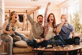 gruppe begeisterten freunden jubeln beim fernsehen im wohnzimmer stockfoto und mehr bilder alkoholisches getränk