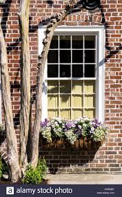 Brick House Window With Planter Box Full Of Flowers And Tree In Foreground