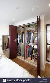 ein offener kleiderschrank mit falttüren in einem