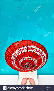 A Bright Red Chinese Paper Umbrella On Diving Board With Womans Feet