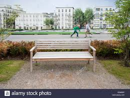 two boys play football behind park bench outdoors in front of a