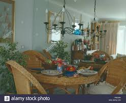Wrought-iron Chandelier Above Wicker Table And Chairs In ...