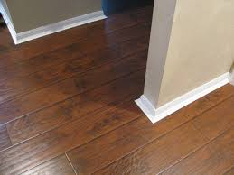 Laminate Floor Transitions To Tiles by Rustic Laminate With Baseboard Detail Home Improvement