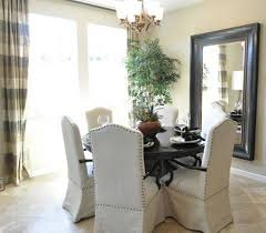 Cozy Dining Room Design Using Slip Cover Parsons Chairs Plus Round Table And Chandelier