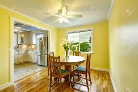 leuchtend gelbe esszimmer mit hölzernen runden tisch und stühlen