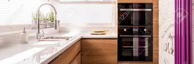 entworfene küche mit weißem hochglanz arbeitsplatte und edelstahl wasserhahn vor violetten heizung