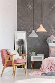vintage rosa stuhl mit weißem kissen im gemütlichen schlafzimmer mit rosa bettwäsche auf kingsize bett designlen und spiegel