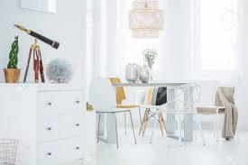 weiße funktionelle wohnung mit kommode esstisch und stühlen