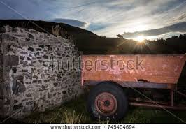 Sunrise Over The Hill With Old Farm Trailer And Stone Wall In Foreground