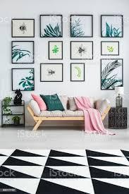 schwarz weiß teppich mit geometrischem muster auf dem boden im hellen wohnzimmer interieur mit hölzernen lounge mit grün und rosa kissen viele plakate