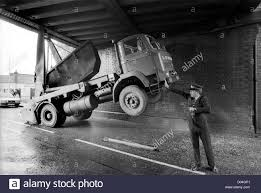a skip lorry wedged underneath a bridge appears to be held up by