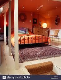orange daunendecke auf metall bett im modernen roten loft