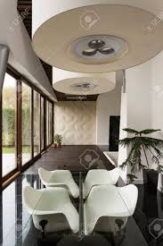 geräumiges esszimmer mit glastisch und modernen stühlen