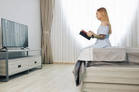 frau die im schlafzimmer vor dem fernseher ruht premium foto