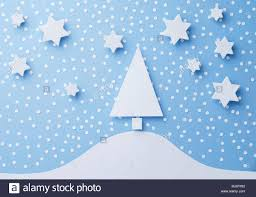 Paper Christmas Tree Stars And Snow Cut From White Over Blue Background Top View